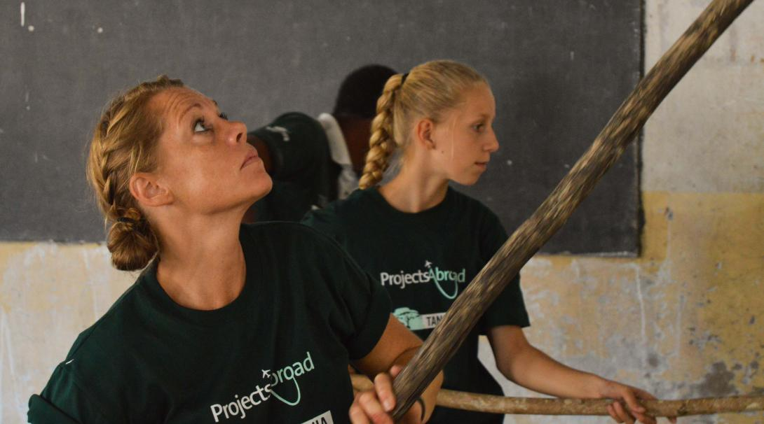 Mother and daughter paint a classroom during their family volunteer holiday in Tanzania